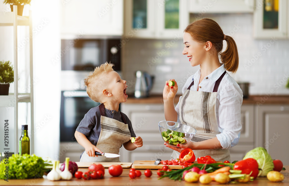 happy family mother with child son preparing vegetable salad .