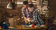 Father And Son Are Woodworking In A Garage At Home.