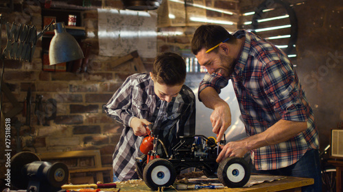 Fotografie, Obraz Father and son are working on a radio control toy car in a garage at home