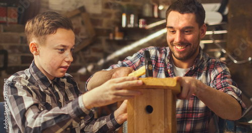 Father and son are making a wooden nesting box in a garage at home Wallpaper Mural