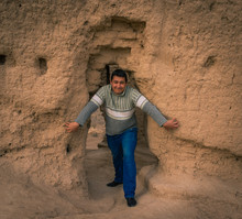 A Young Local Man In Blue Jeans And Grey Sweater At The Entrance Door To An Ancient Asian Sandstone Castle At Midday.