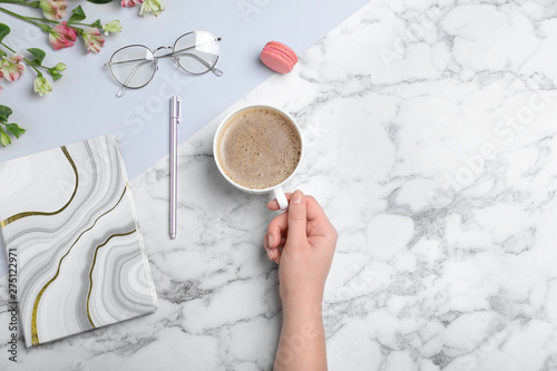 Cafe Woman with cup of coffee and stationery at marble table, top view. Space for text