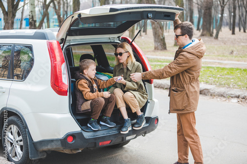 Fényképezés  young family packing for car travel. putting bags into trunk