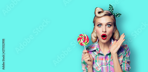 Photo of beautiful very surprised woman with lollipop, in pinup style, over blue Wallpaper Mural