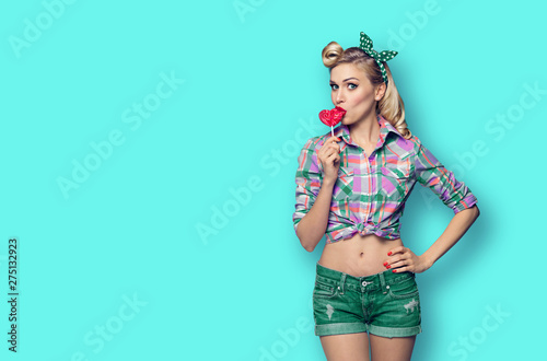 Photo Photo of young woman eating heart shape lollipop, dressed in pinup style, over g