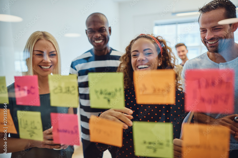 Fototapeta Laughing work colleagues brainstorming together in an office