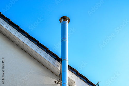 Fotomural Stainless steel chimney and parts of a roof in front of a bright blue sky