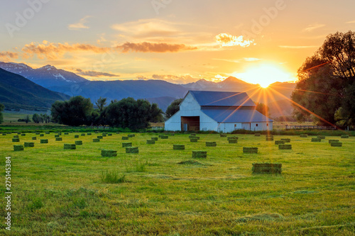 Obraz na plátně Rural sunset with hay bales and an old barn in the countryside, Utah, USA