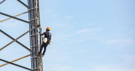 Telecom maintenance. Worker climber on tower against blue sky background