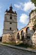 Bell tower, part of the wall and a forged iron gate on the background of the blue sky. Ruins of the Armenian Church of St. Nicholas of the XV century, Kamianets-Podilskyi, Ukraine.