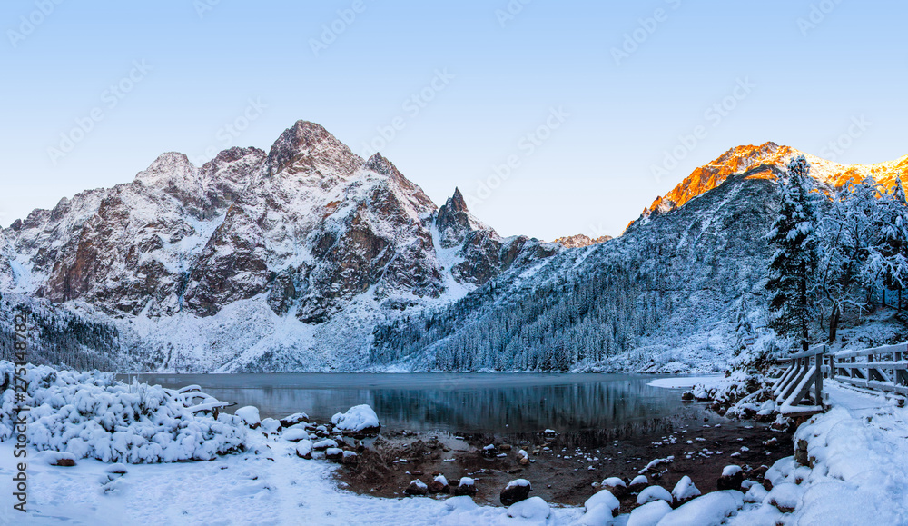 Fototapety, obrazy: Winter mountains. Snowy mountain on Morskie Oko icy lake. Winter rocks on clear morning