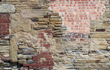 Large Old Wall Made Of Mixed Bricks And Stone With Many Jumbled Patched And Uneven Repairs