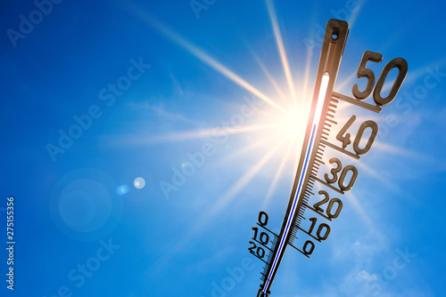 Poster Ouest sauvage Hot summer or heat wave background, bright sun on blue sky with thermometer
