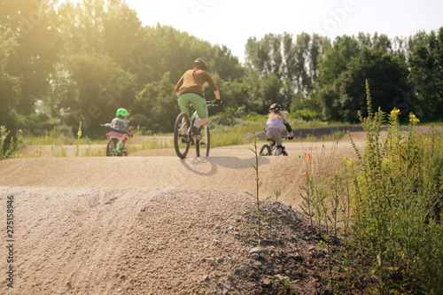 Fotomural  mother and two daughters riding bike together on a bicycle dirt track in bright