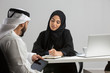 Arab businessman and businesswoman discussing.