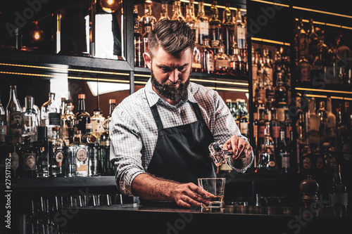 Diligent serious barman is preparing alcoholic beverege for customer Canvas Print