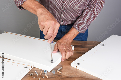 Poster Ecole de Danse A man assembling a DIY piece of furniture. Person is using a screwdriver inserting a piece of hardware