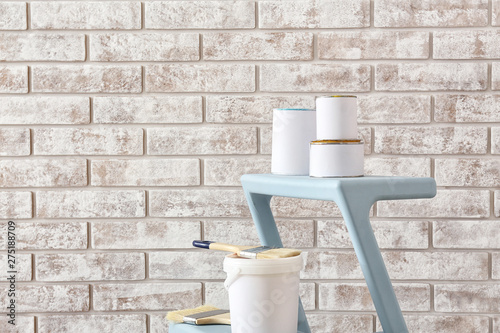 Cans of paint with supplies on step ladder near brick wall Wallpaper Mural