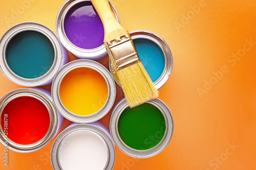 Photo  Cans of paints and brush on color background