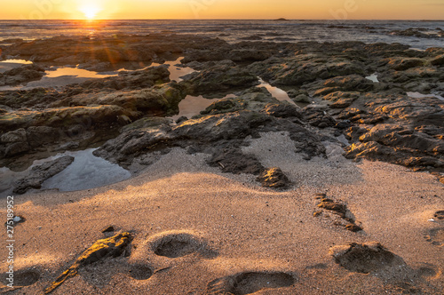 Sunset across the beach sands with footsteps