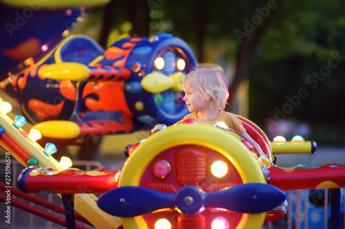 Little boy having fun on attraction in public park Tablou Canvas