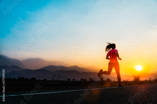 Foto auf AluDibond Jogging Young woman enjoys running outside with beautiful summer evening in the countryside.