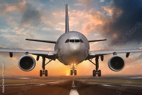 Airplane landing on airport runways during sunset Canvas Print