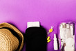 canvas print picture - Set for flight small bottles with cosmetics, hat, earplugs, nasal spray, air ticket and documents on purple background. Top view, copy space