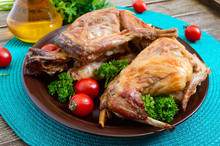 Whole Baked Rabbit With Greens And Tomatoes On A Plate. Tasty Dietary Meat.