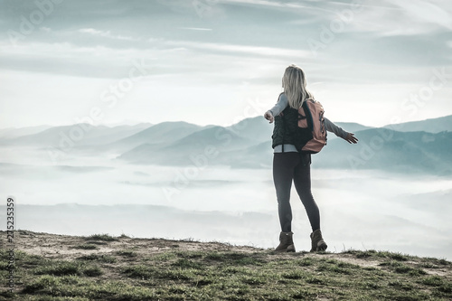 Fotografie, Obraz  Happy woman tourist stay on the green grass on the peak of mount