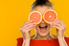 Young Beautiful Woman Holding Slices Of Grapefruit In Front Of Her Eyes On Yellow Background