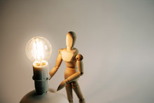 Wooden Puppet With Light Bulb In White Background.Wooden Mannequin Figure Taking The First Step  To His Goal- Career, Growth Or Development Concept.