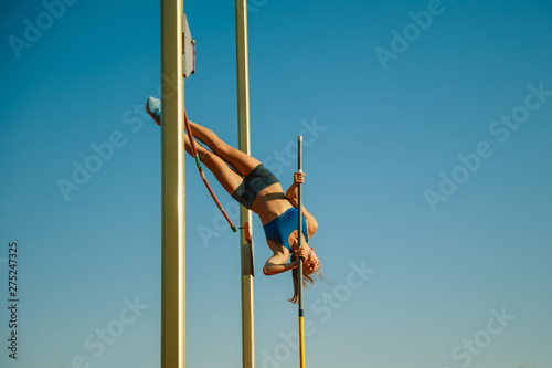 Fotografía  Professional female pole vaulter training at the stadium in sunny day