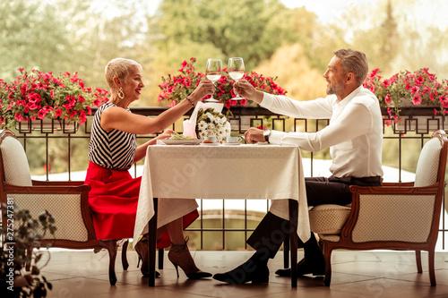 Obraz na plátně  Businessmen clanging glass of white wine having romantic date