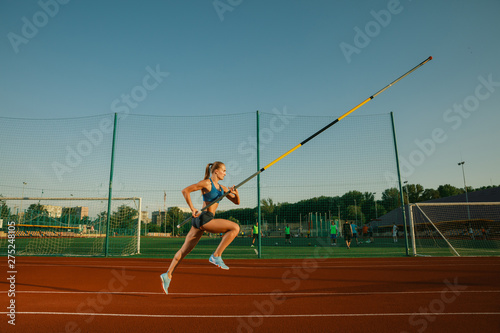 Fototapeta Professional female pole vaulter training at the stadium in sunny day. Fit female model practicing in high jumps outdoors. Concept of sport, activity, healthy lifestyle, action, movement, motion. obraz