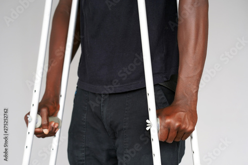 Cuadros en Lienzo Hand african man on crutches on a gray background