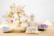 Calming Meditation Background With Sitting Meditating Buddha, Crystal Clusters( Purple Amethyst And Blue Celestite) And Gemstone Wire Tree White Minimalist Background With Copy Space.