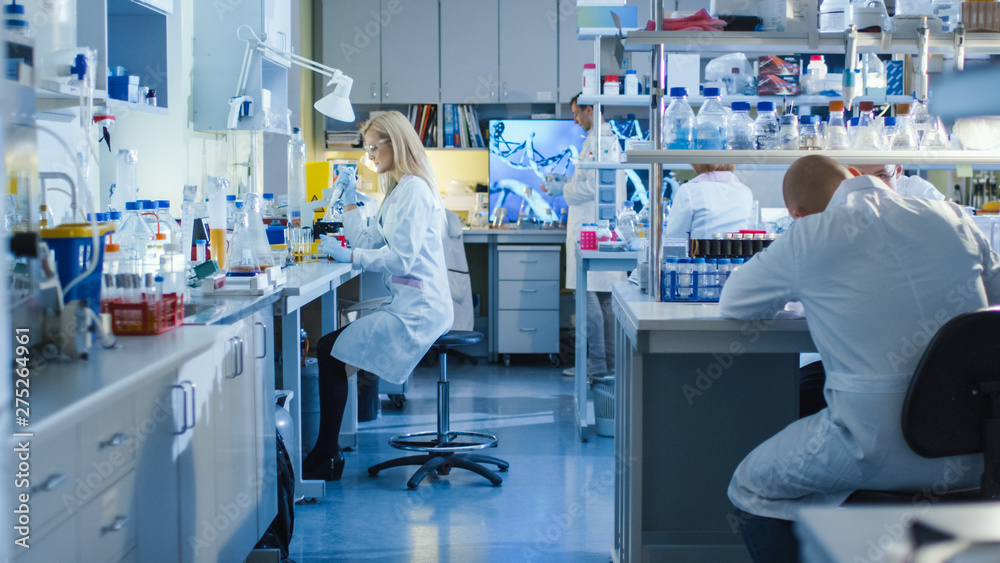 Fototapety, obrazy: Genetic Research Scientists Work with Medical Equipment in a High Tech Research Laboratory. Female Scientist is using a Micro Pipette While Working with Colleagues.