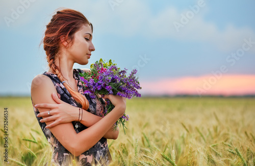 Платно  Cute attractive girl with a bouquet of colorful flowers in her hands