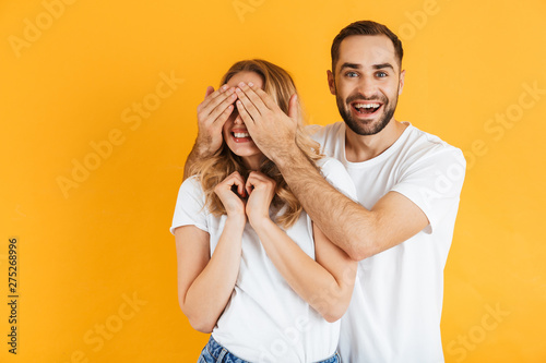 Obraz na plátně  Excited cheerful young couple standing isolated