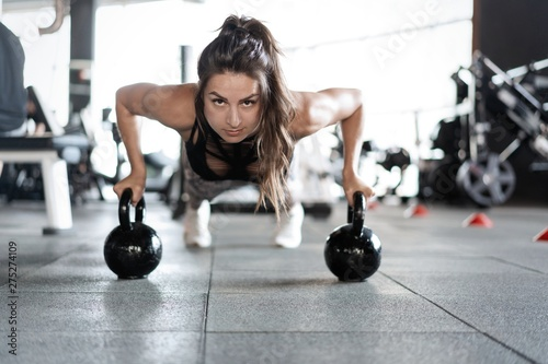 Sportive woman doing push-ups in the gym using kettlebells. - 275274109