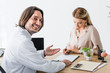 selective focus of happy doctor looking at camera while patient signing document