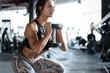 Leinwandbild Motiv Athletic young woman fitness model doing squats exercise, concept sport healthy lifestyle.