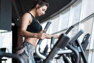 Beautiful gym woman exercising on a cardio machine smiling.