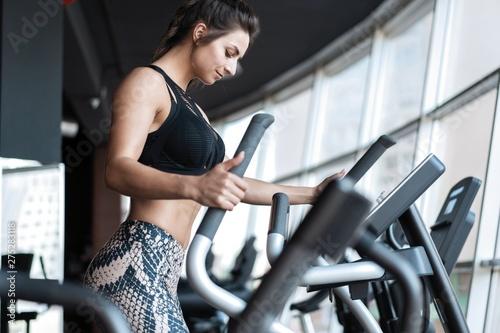 plakat Beautiful gym woman exercising on a cardio machine smiling.