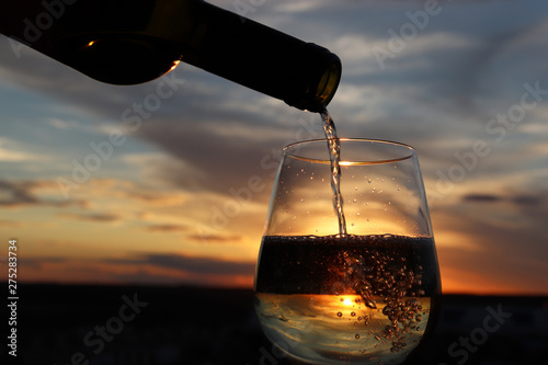 Foto auf Leinwand Schwarz Wine pouring from a bottle into drinking glass on colorful sunset background, orange sun is shining through the golden bubbles. Concept of romantic dinner, celebration, alcohol drink