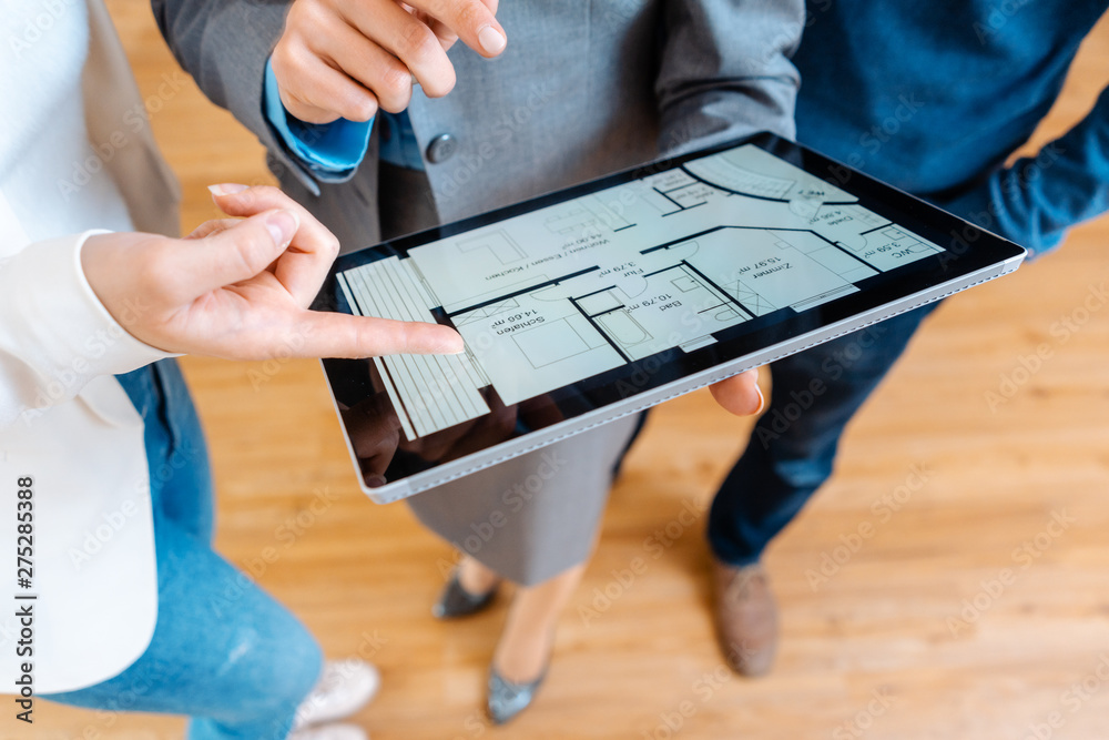 Fototapety, obrazy: Realtor explaining floor plan to couple buying a house