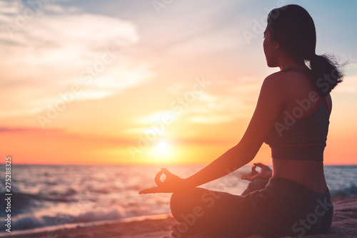 Foto Silhouette young woman practicing yoga on the beach at sunset.