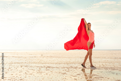 Photographie  A girl in a coral swimsuit on the background of the salty sea of the lake