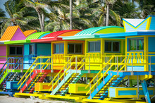 Colorful Scenic Morning View Of Brightly Painted Lifeguard Towers With Coconut Palm Trees On The South Beach Promenade In Miami, Florida, USA